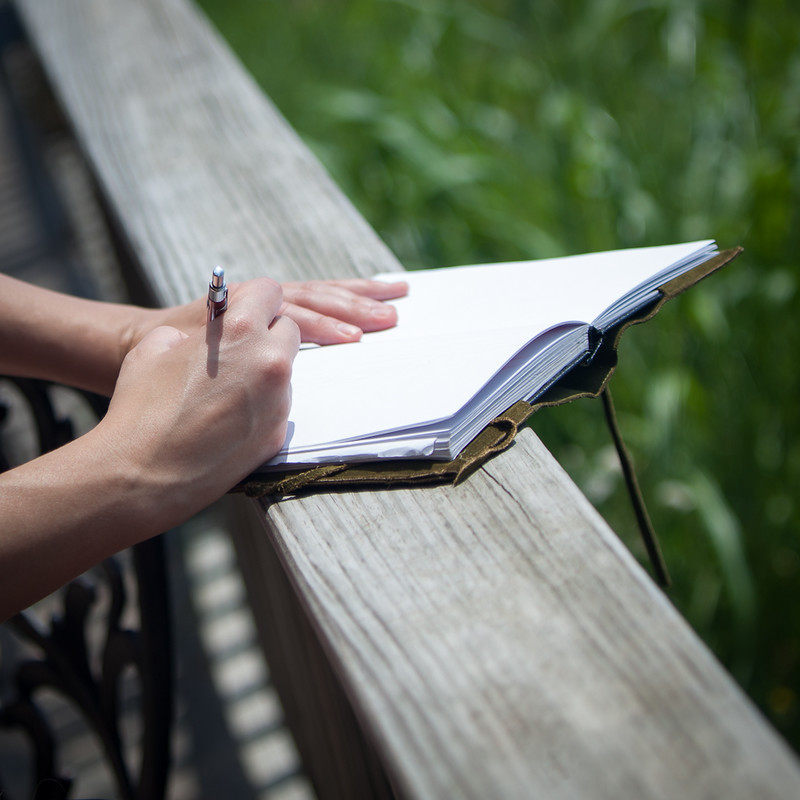 a person writing journal on a white paper