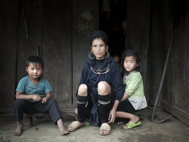 an indigenous mohter sitting with her two children infront of their home