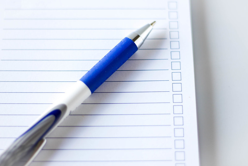 pen placed on top of a to do list white paper
