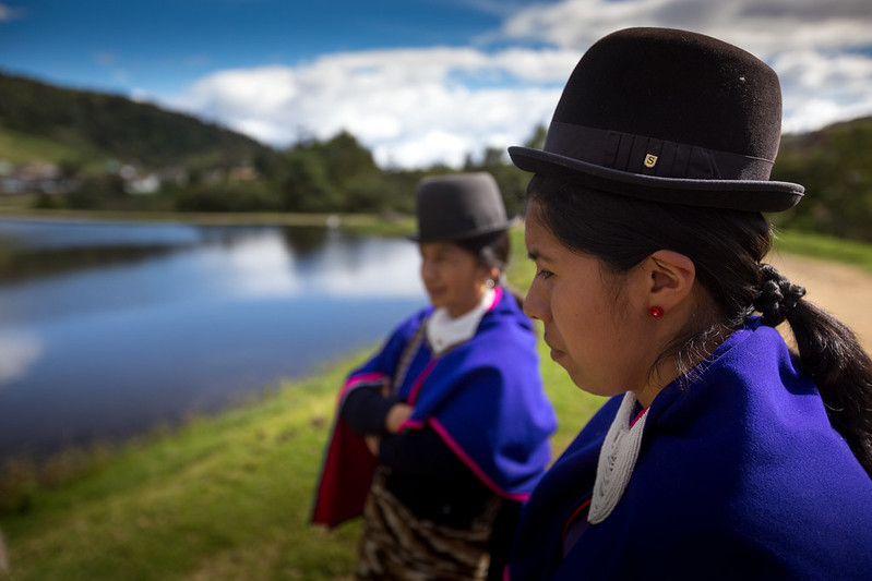 two indigenous women standing next to each other in front of a lake