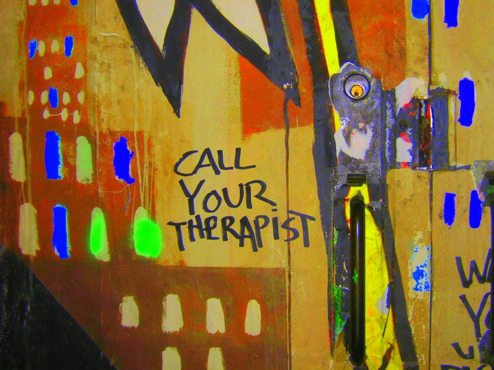 """a graffiti drawing on a wall with a sentence read """"Call Your Therapist"""""""