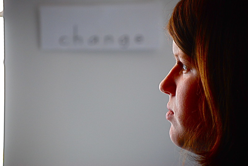 """woman looking at a glass with the word """"change"""" in the background"""