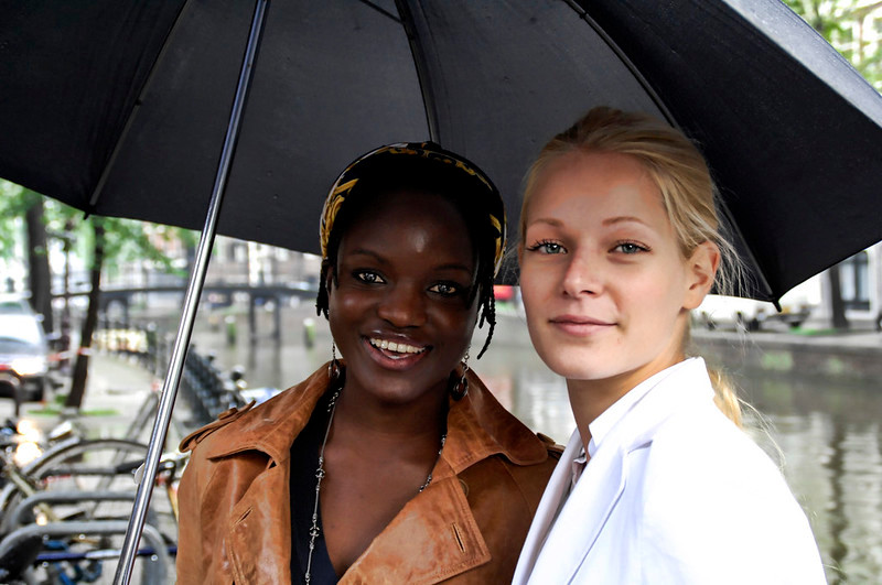 one black woman wearing light brown leather jacket and one white woman wearing white jacket standing together under a black umbrella