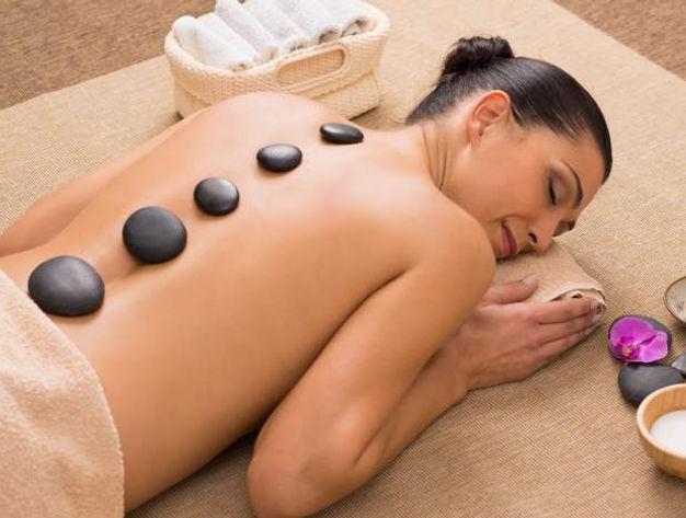 Jeune femme alliongée sur le ventre en train de faire un massage aux pierres chaudes à Genève