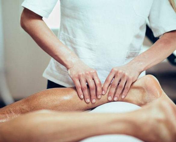 Thérapeute éffectuant un massage sportif au niveau des mollets