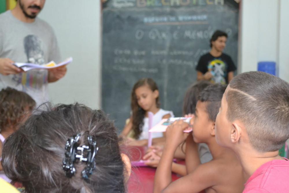 Memórias pontuais: leitura e pergunta O que é memória. Crianças na mesa, Paulo lendo histórias, e Carlos próximo a lousa no fundo.