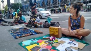 Vendas na Paulista: Avenida Paulista, São Paulo. Ana está sentada, livros expostos no chão.