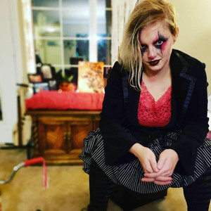Image of  a woman dress up for halloween as dark clown.