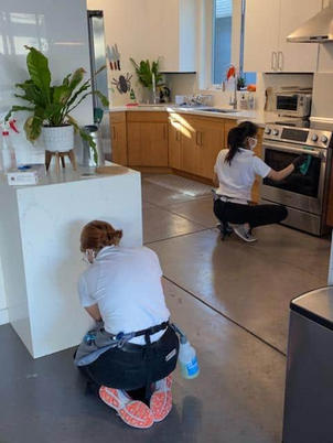 Two women cleaning the kitchen in home .