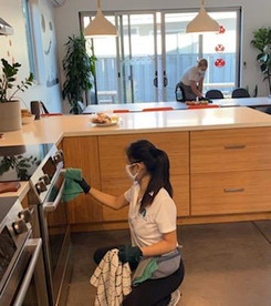 A woman in the foreground cleaning an ov