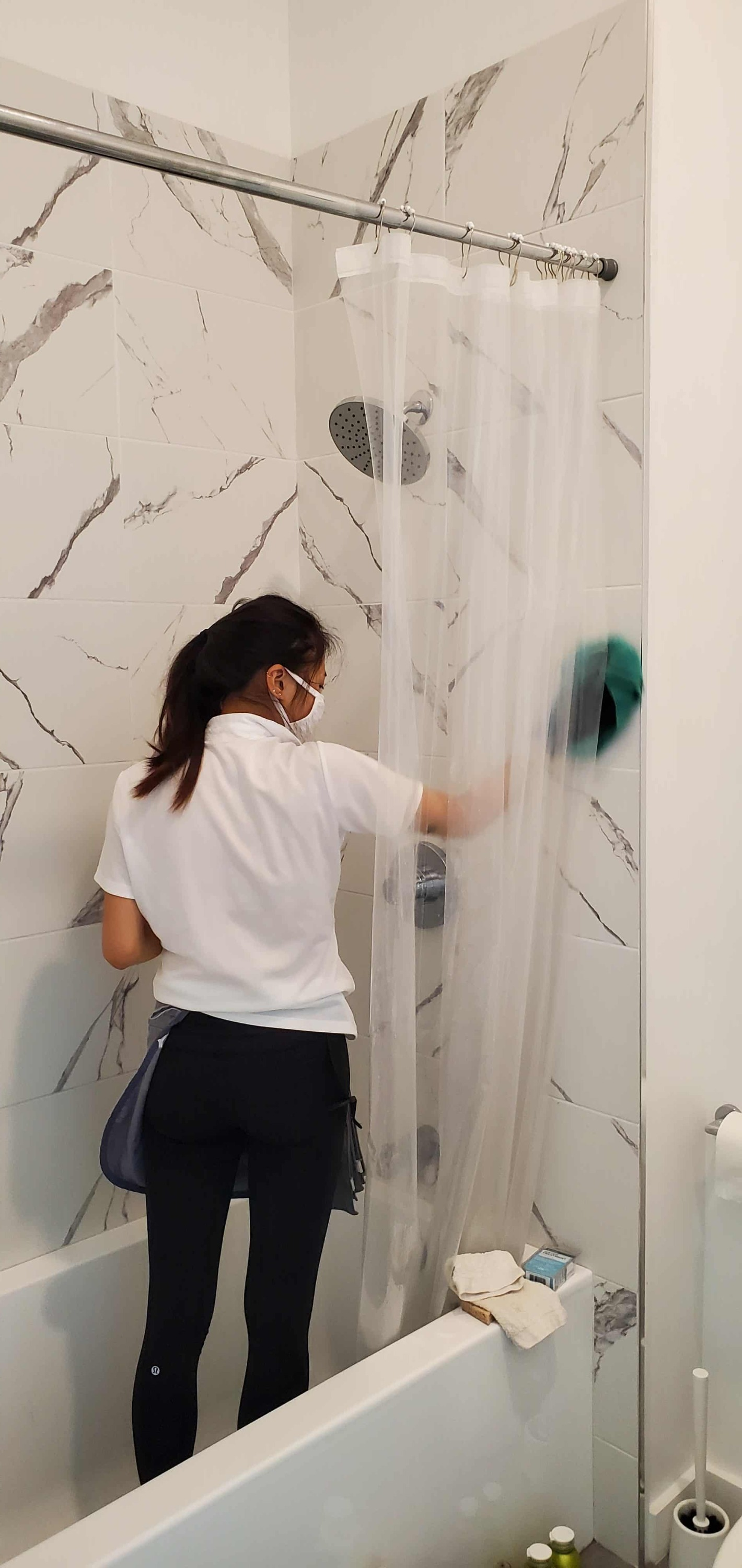 woman cleaner cleaning the tile in on shower wall in a bathroom