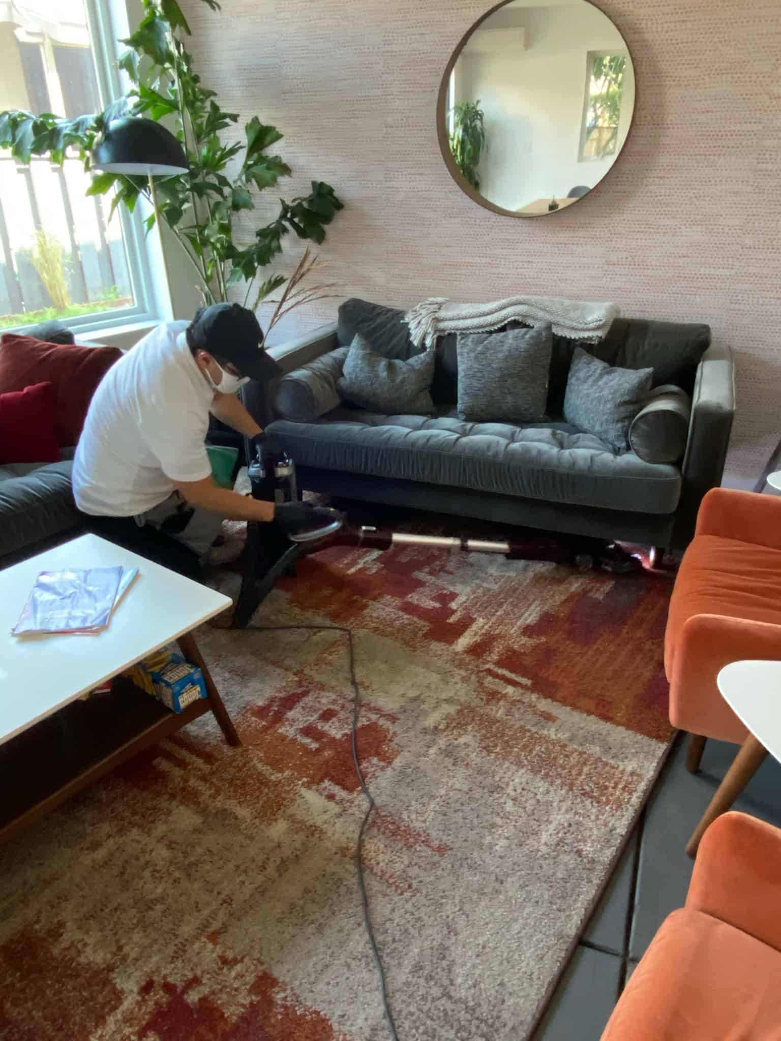male cleaner vacuuming underneath a couch in the living room