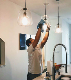 Male cleaner cleaning the light fixtures