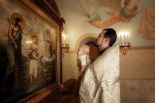 Таинство крещение, малышу показывают картину