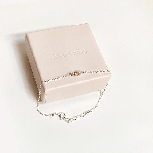 Bracelet en argent avec une perle rose.