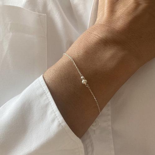 Bracelet en argent avec une perle blanche.