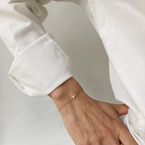 Bracelet en argent doré avec une perle blanche.