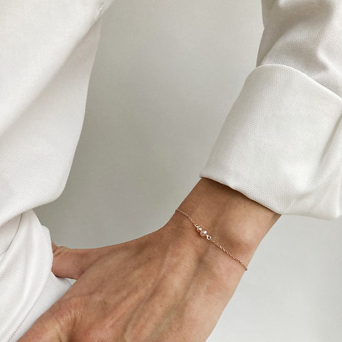 Bracelet en argent doré avec une perle rose.