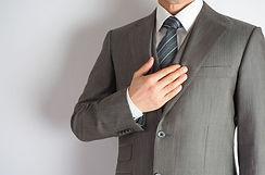 胸に手を当てるスーツの男性