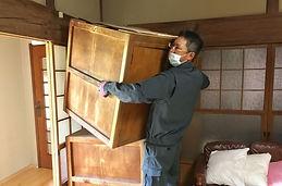 荷物を運ぶ作業服の男性