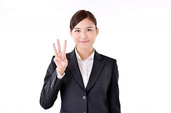指を三本立てるスーツの女性