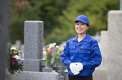 お墓の前で微笑む女性