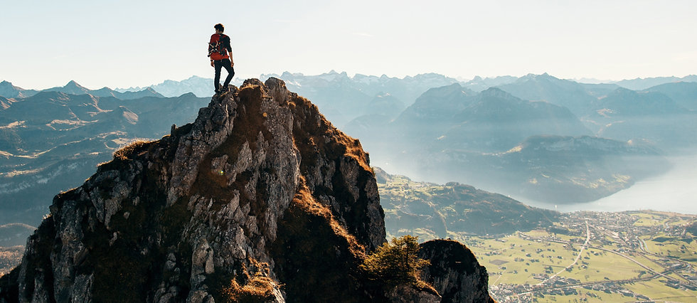 man climbing to the top of the mountain | Pendragon Consulting LLC