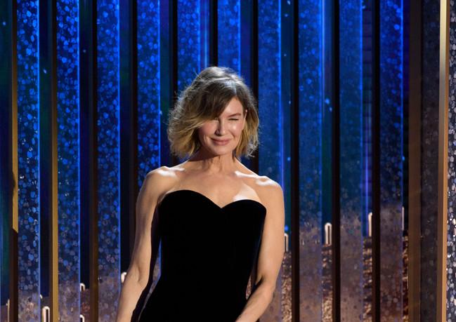 Renee Zellwegger com um vestido preto Giorgio Armani Privé apresenta o globo de ouro pela melhor actuação, como Melhor Actor – Drama no 78th Annual Golden Globe Awards no the Beverly Hilton, em Beverly Hills, CA. Fotografia: HFPA Photographer.