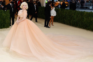 """A cantora Billie Eilish, que faz parte de coanfitriões do MET Gala 2021, com um vestido Oscar de la Renta. A cantora foi comparada com Marilyn Monroe, como uma princesa da Disney com jóias diamantes da Cartier High Jewelry em honra Marilyn Monroe. O seu aspecto é absolutamente deslumbrante.  O seu cabelo loiro curto com um look clássico de Hollywood  Eilish disse que a inspiração foi """"Barbie de férias""""."""