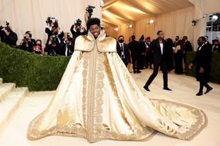 A primeira peça de Lil Nas X foi esta dramática capa dourada de Donatella Versace. O rapper optou por usar um conjunto dramático, concebido por Donatella Versace, que era o equivalente à de uma boneca Matryoshka. Uma roupa, que transformou em 3 conjuntos.  Para a sua primeira revelação, Lil Nas X usou uma capa ornamentada que estava coberta de contas douradas. O desenho tinha um toque real. A capa tinha uma cauda longa e fluente que não podia deixar de chamar a atenção no tapete vermelho.