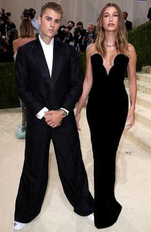 """Hailey, com um vestido preto justo ao corpo YSL, enquanto Justin, posava num fato preto clássico em homenagem ao tema deste ano, """"Na América"""": Um Léxico da Moda"""". O look mínimo de Hailey Bieber apresentava um colar de diamantes azuis inspirado em Tiffany Art Deco, assim como alguns anéis de Tiffany para combinar com o seu deslumbrante vestido Saint Laurent."""