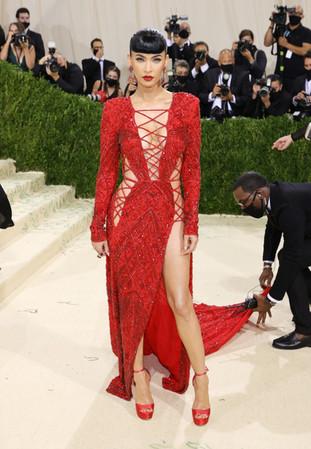 Megan Fox com um vestido de renda de Dundas vermelho com mangas compridas e com brincos de pedras preciosas coloridas da Lorraine Schwartz. O vestido de renda da Dundas da actriz, estilizado por Maeve Reilly.