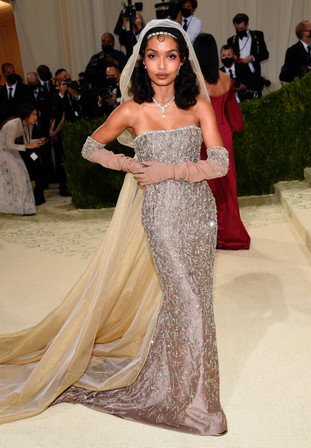 """Yara Shahidi com um vestido Dior Haute Couture e jóias Cartier """"Sixième Sens High Jewelry"""", com um colar em ouro branco, platina, diamantes brancos e amarelos e ônix, parte do qual se destaca e é usado no seu cabelo e os brincos também são Cartier High Jewelry em platina e diamantes. Yara Shahidi queria que o seu look tinha com objectivo prestar homenagem a uma artista negra americana, Josephine Baker. Shahidi após o evento, partilhou o seguinte. """"Só espero ter sido capaz de o fazer"""". Baker é uma musa adequada para Shahidi. Nos anos 20, Baker percorreu o país dançando com uma companhia itinerante antes de aterrar na cidade de Nova Iorque para actuar na Broadway. Mais tarde, Baker mudou-se para França, onde começou a cantar, tornando-se cidadã francesa em 1937."""