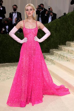 Nicola Peltz com um vestido de Valentino e com  brincos compridos com diamantes.