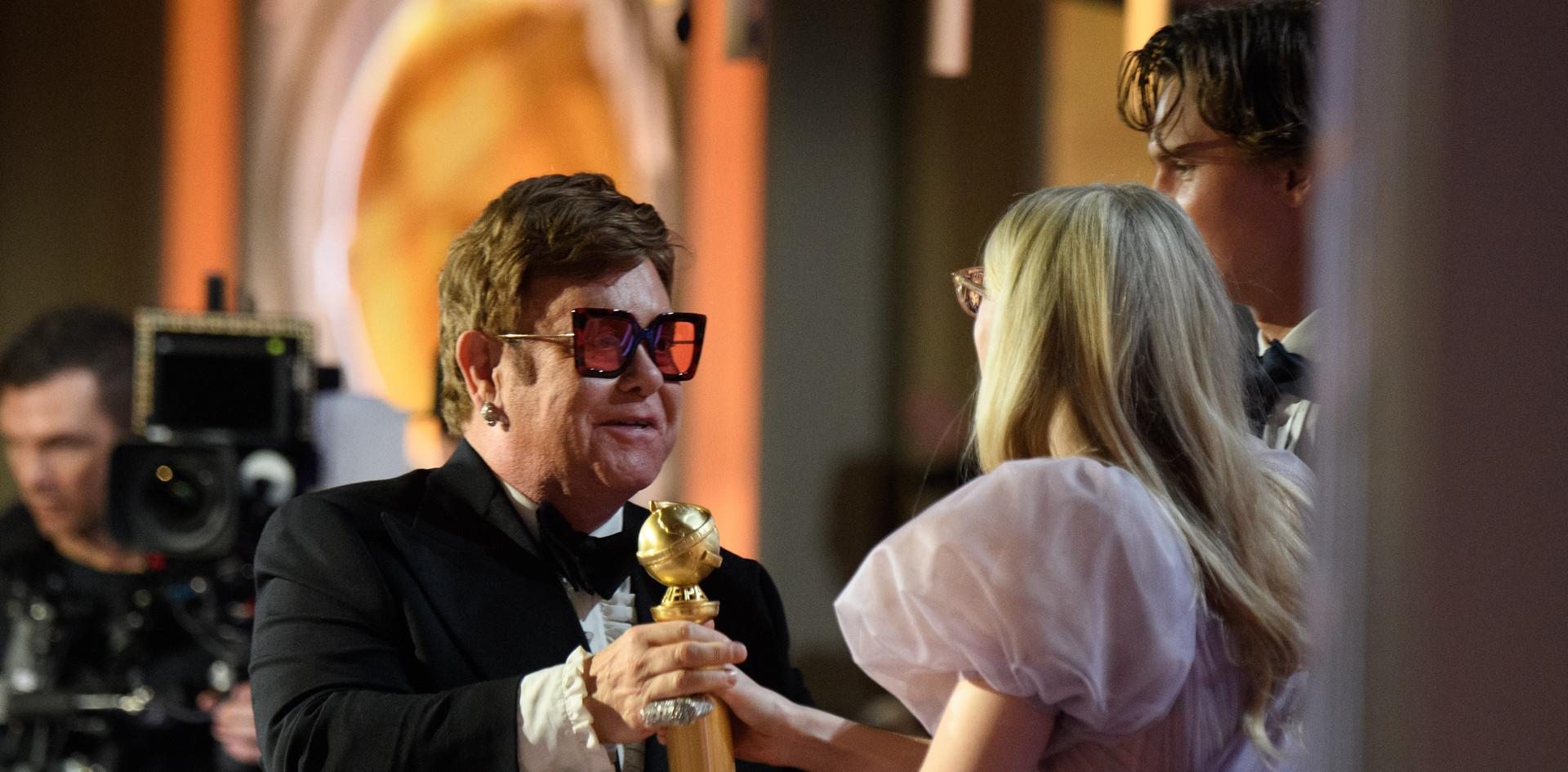 """Elton John recebendo de Ansel Elgort e de Dakota Fanning o Golden Globe pela Melhor Música Original do Filme: """"Rocketman"""", na cerimónia da entrega dos Golden Globes no 77th Annual Golden Globes Awards no Beverly Hilton em Beverly Hills, CA. Fotografia: HFPA Photographer."""