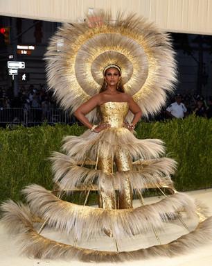 O modelo dourado de Iman Glowed é da autoria da dupla Dolce & Gabbana e Harris Reed.  Corpete e calças em brocado, com uma sobre-saia em gaiola de penas douradas e uma peça de cabeça a condizer, desenhada numa colaboração entre Dolce & Gabbana e o designer britânico-americano Harris Reed. E o chapéu, foi feito em colaboração com Vivienne Lake. Iman usou joias Fred Leighton e Kwiat, incluindo: Pingentes multicoloridos de citrinos e diamantes em ouro amarelo e citrinos de Fred Leighton, e  pulseira de ametistas e diamantes Reflections Cuff Bracelet de Trabert & Hoeffer Mauboussin, cerca de 1935, diamante Fred Leighton e pulseira de ouro amarelo de Boivin, cerca de 1930 e um anel de diamante amarelo sobre platina Cocktail Ring, assinado por Fred Leighton e Kwiat .