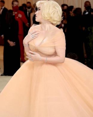 """A cantora Billie Eilish, que faz parte de coanfitriões do MET Gala 2021, com um vestido Oscar de la Renta. A cantora foi comparada com Marilyn Monroe, como uma princesa da Disney com jóias diamantes da Cartier High Jewelry, em honra Marilyn Monroe. O seu aspecto é absolutamente deslumbrante. O seu cabelo loiro curto com um look clássico de Hollywood.  Eilish disse que a inspiração foi """"Barbie de férias""""."""
