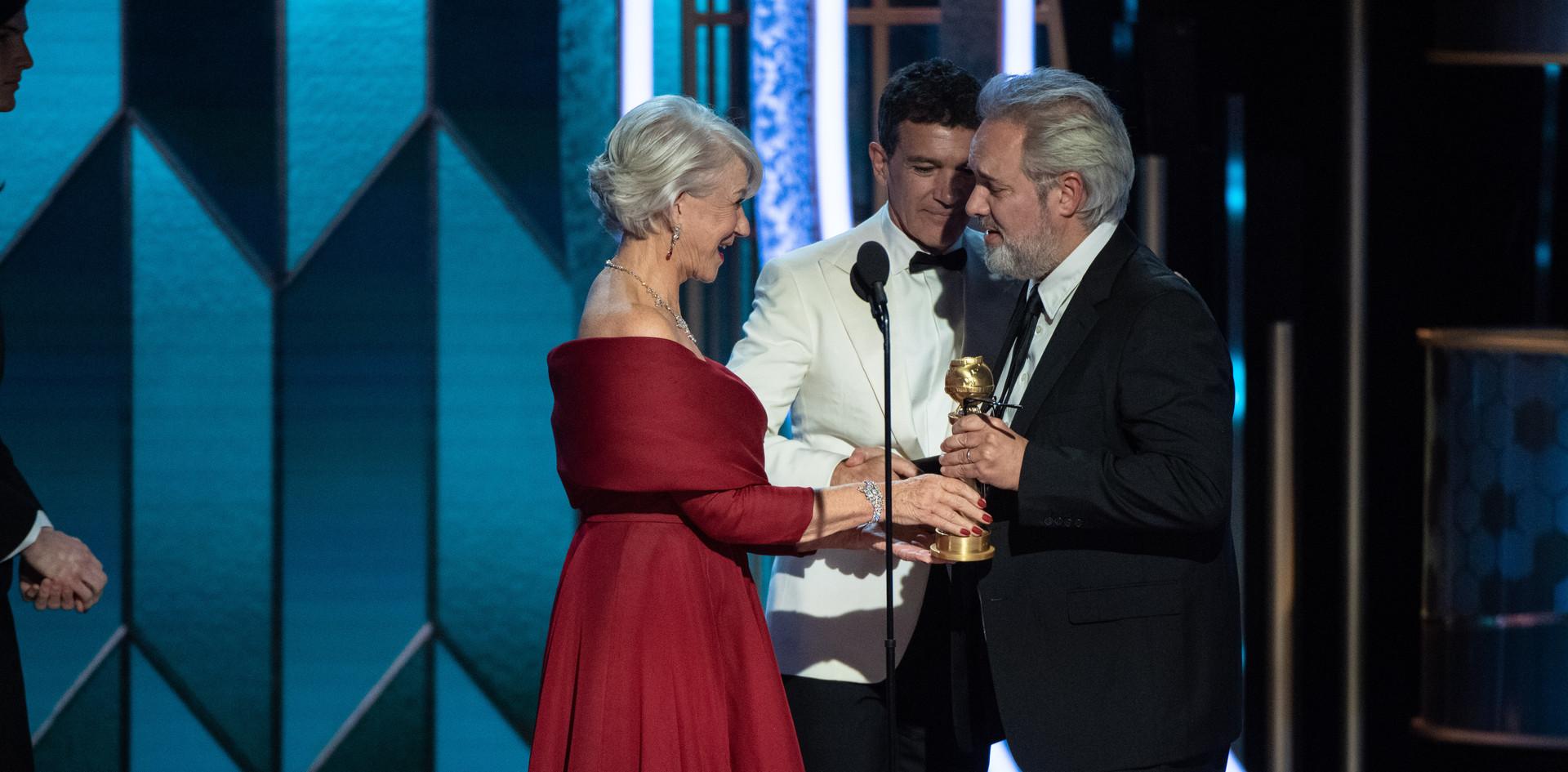 """Sam Mendes recebendo de Helen Mirren e Antonio Banderas o Golden Globe, como Melhor Realizador do Filme:""""1917"""", na cerimónia da entrega dos Golden Globes no 77th Annual Golden Globes Awards no Beverly Hilton em Beverly Hills, CA. Fotografia: HFPA Photographer."""