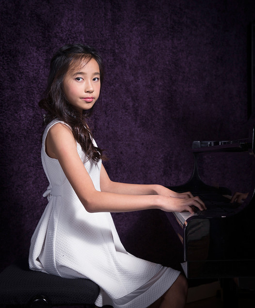 A studio portrait of a girl in white dress playing piano