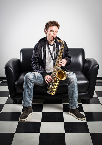 Studio Portrait of a young man playing saxophone