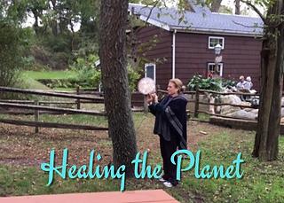 Woman giving reiki healing to trees.