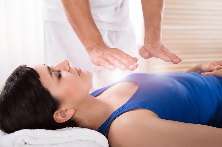 woman receiving reiki treatment on massage table