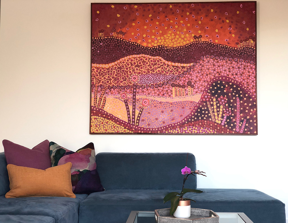 The cushions used here contrast with the sofa but pick up the colours in the art on the wall