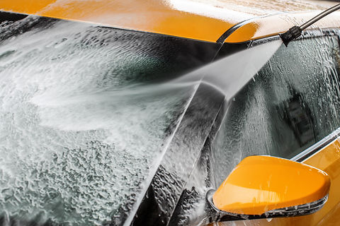 detailing orange car with pressure washer