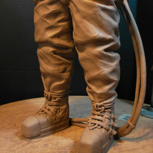 The rivets in the boots can be seen, along with the rope wrapped around the ankles and tucked under the 3 leather straps