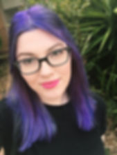 Meredith, a woman with bright purple hair, black glasses and bright pink lipstick smiles at the camera.