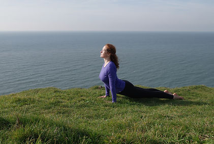 Woman doing yoga outdoors next to sea in Wales