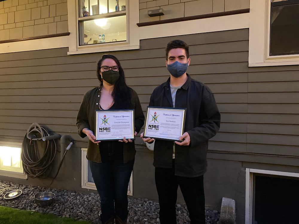 NSBE Pro-PDX's first interns display their internship completion certificate from NSBE Pro-PDX with masks on in front of a house..