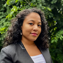 J'Reyesha (Jay) Brannon in a gray suite standing in front of a green tree