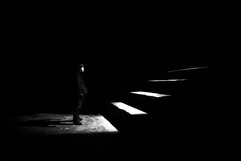 grayscale photo of man standing in front of stairs_edited.jpg